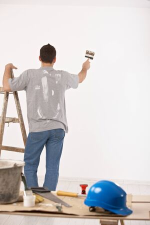beside: Guy painting wall white with paint brush, standing beside ladder. Stock Photo