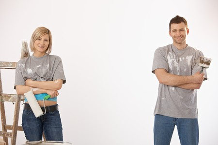 Portrait of smiling couple painting at home, holding paint roller and brush, looking at camera. photo