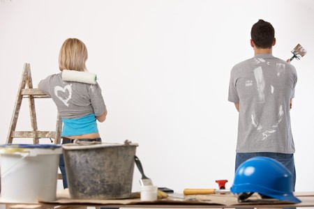 RENOVATE: Portrait of couple painting at home, holding paint roller and brush, looking at wall.
