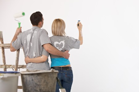 Couple standing together, embracing, holding paint brush and paint roller, painting wall. photo