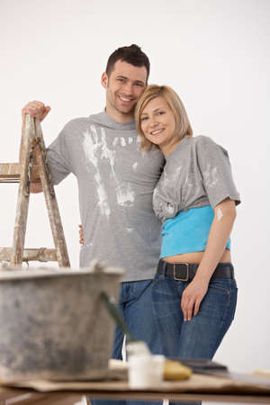 Portrait of happy couple standing together after painting their home, looking at camera, smiling. Stock Photo - 7015808