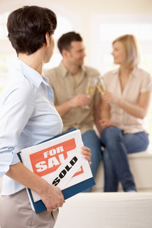Estate agent in focus holding for sale sign looking at celebrating couple in background. Stock Photo - 7015733