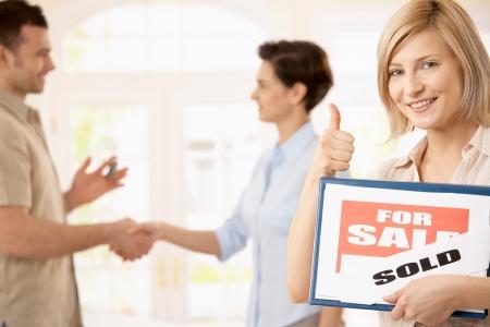 real estate sold: Mujer feliz celebraci�n para la firma de venta dando el pulgar arriba, hombre sonriente, agitando las manos con el agente inmobiliario en segundo plano.