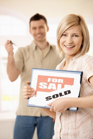 Happy woman holding for sale sign, laughing man in background holding keys of new house. Stock Photo - 7015811