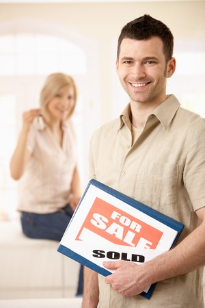 Happy man standing with for sale sign, girlfriend in background holding keys of house. Stock Photo - 7015836