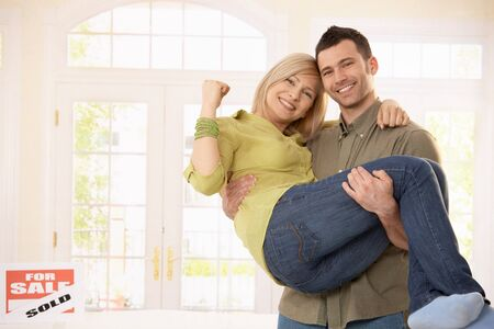 vendiendo: Hombre feliz llevando la mujer sonriente en brazos en nuevo hogar. Foto de archivo