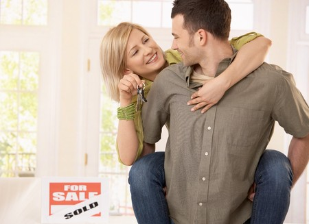 people buying: Young man taking smiling girlfriend on back into new house, woman holding keys.