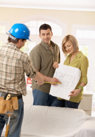 renovation de maison: Sourire couple discuter au sol plan de maison neuve avec le constructeur.
