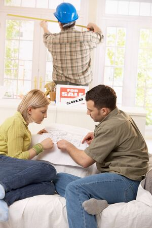 Young couple sitting in new house, looking at ground plan, builder measuring window size in background. Stock Photo - 7015861