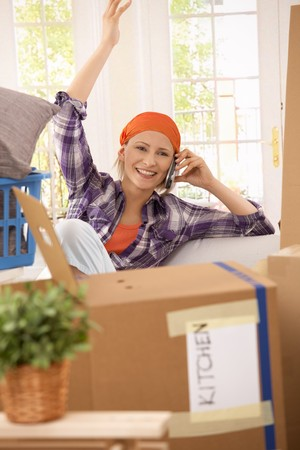 Happy woman talking on mobile phone while moving house. photo