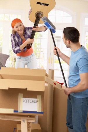 Laughing couple pretending to fight with guitar and broom at break of house moving. photo