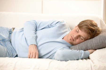 taking nap: Tired young man sleeping on couch, taking afternoon nap. Stock Photo