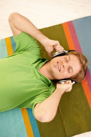 Happy guy lying on colorful carpet listening to music via headphones with closed eyes. Stock Photo - 7016174