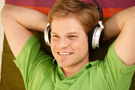 Portrait of young man with headphones, smiling happily. Stock Photo - 7016154