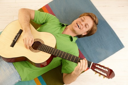 Happy young man lying on floor holding guitar, smiling in high angle view. photo