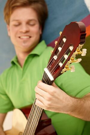 Smiling man playing guitar, focus on hand and neck of instrument. photo