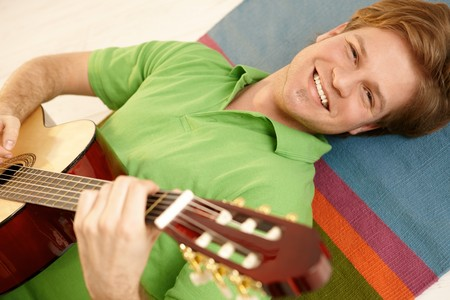 Portrait of handsome guy playing guitar lying on floor. photo