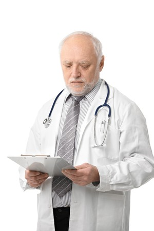 Portrait of senior doctor looking at papers, photo isolated on white.