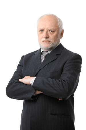 unsmiling: Portrait of serious senior businessman cutout, white background.