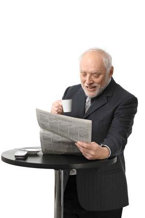 news stand: Portrait of happy senior businessman drinking coffee reading newspaper, laughing, white background.