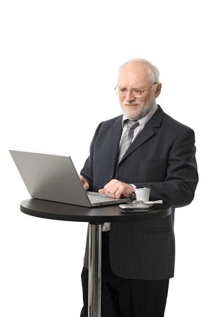 Portrait of happy senior businessman using laptop on coffee table, isolated on white. photo