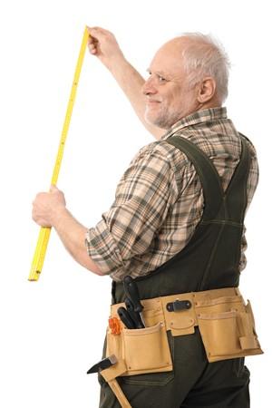 Elderly man measuring during home renovation, smiling, cutout. photo