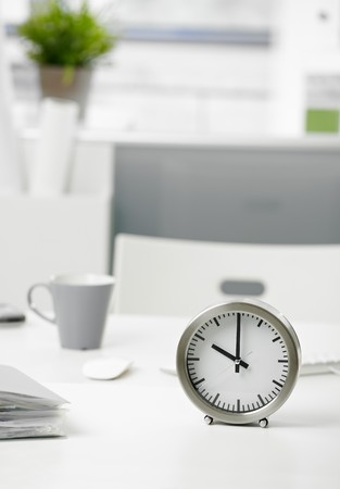 office life: Close-up photo of clock on office desk.