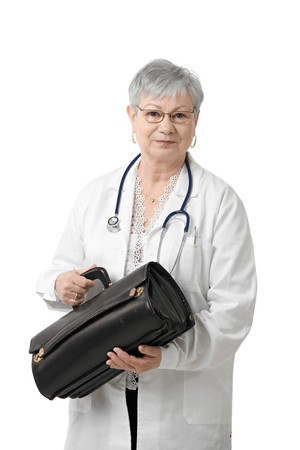 Senior physician with doctors bag, looking at camera, isolated on white. photo