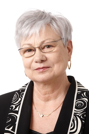 older person: Closeup portrait of senior lady wearing glasses, smiling at camera. Stock Photo