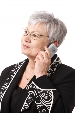 Closeup portrait of senior lady wearing glasses, using mobile phone, isolated on white. photo