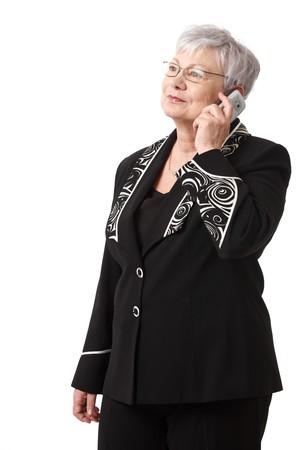 Portrait of senior woman using mobile phone, smiling, isolated on white. Stock Photo - 7003261