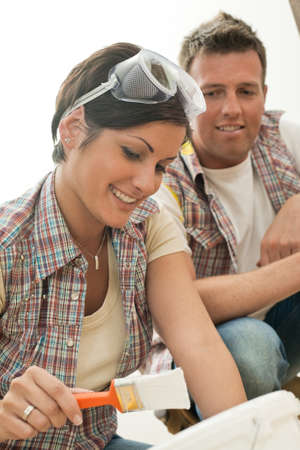 Smiling pretty woman holding paint brush, man looking in background. Stock Photo - 7015749