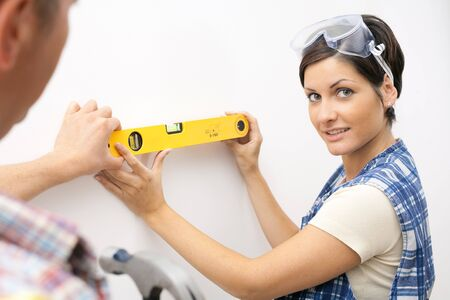 Portrait of smiling woman working with spirit level, man helping to hold at wall. photo