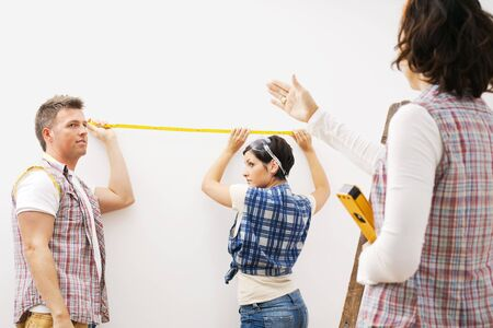 Couple holding measuring stick at wall, female friend standing on ladder holding spirit level directing.  photo
