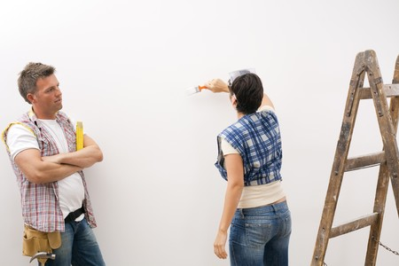 Woman painting white wall, man focusing on work standing with folded arms. Stock Photo - 7003252