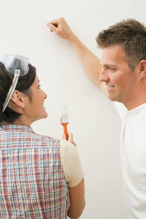 Happy couple at home improvement looking at each other, painting wall, woman holding paint brush. photo