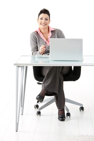 Happy businesswoman sitting at office desk, using laptop computer smiling. Isolated on white background. photo
