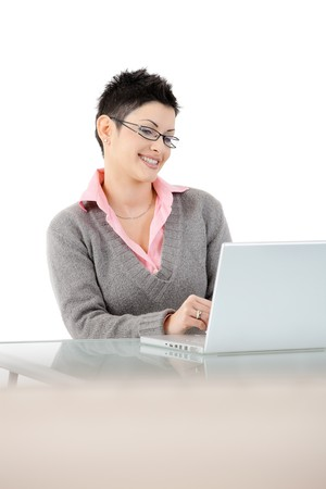 Happy businesswoman stitting at office desk using laptop computer, smiling. Isolated on white background. Stock Photo - 7016259