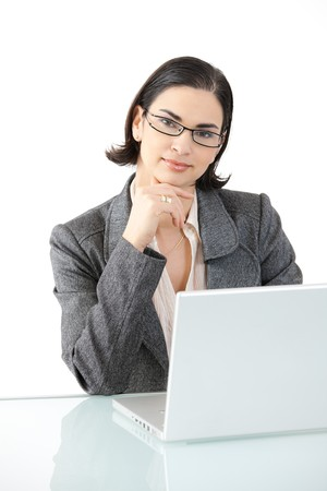 Young businesswoman sitting at office desk, using laptop computer, looking at camera, smiling. Isolated on white background. photo
