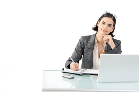Happy businesswoman sitting at office desk working on laptop computer, smiling. Isolated on white background. photo