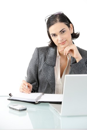 Young businesswoman sitting at office desk with laptop computer and organizer, looking at camera, smiling. Isolated on white background. photo