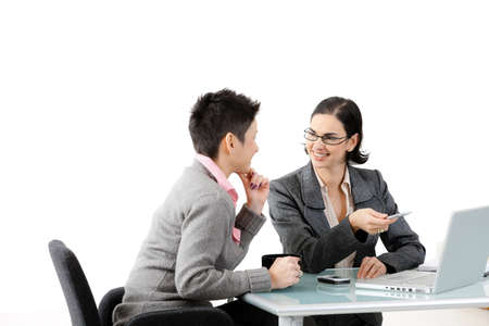 Young businesswomen sitting at office desk, looking at each other, smiling. Isolated on white. photo