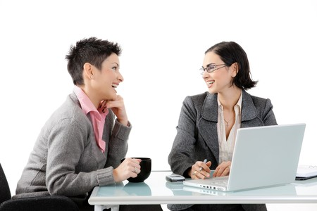 two people talking: Young businesswomen sitting at office desk, looking at each other, smiling. Isolated on white.
