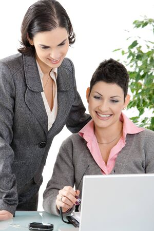Happy businesswomen looking at laptop computer screen, smiling. photo