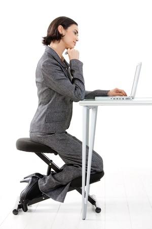 mujer arrodillada: Young feliz empresaria trabajando en silla de rodillas, sonriente, aislados en blanco.