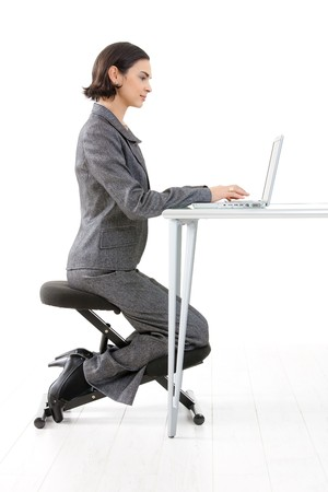 Young happy businesswoman working on kneeling chair, smiling, isolated on white. Stock Photo - 7016244