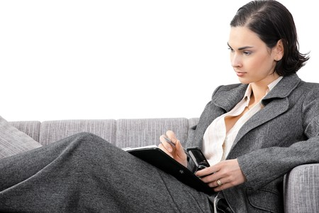 Businesswoman wearing grey suit lying on couch, writing notes in presonal organizer. Isolated on white. photo