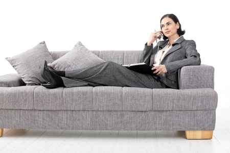 Relaxed businesswoman wearing grey suit lying on couch, talking on mobile phone. Isolated on white. photo