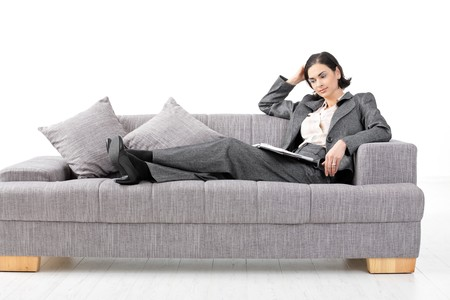 Young businesswoman sitting on sofa, working. Isolated on white background. photo