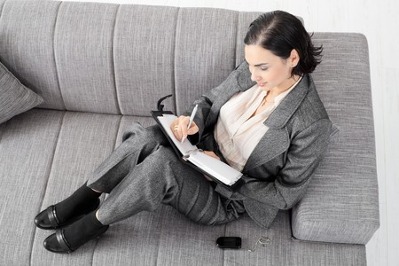 Young businesswoman sitting on sofa, working, overhead view. photo